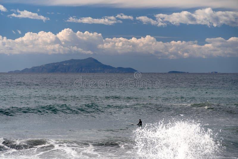 De surfer neemt een golf, op een surfplank, glijdt langs de golf, op de achtergrond van de berg, Sorrento Itali? stock foto's