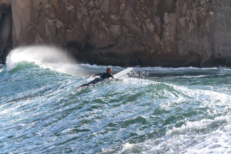 De surfer neemt een golf, op een surfplank, glijdt langs de golf, op de achtergrond van de berg, Sorrento Itali? stock foto