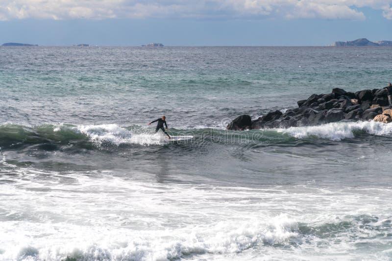 De surfer neemt een golf, op een surfplank, glijdt langs de golf, op de achtergrond van de berg, Sorrento Itali? stock afbeelding