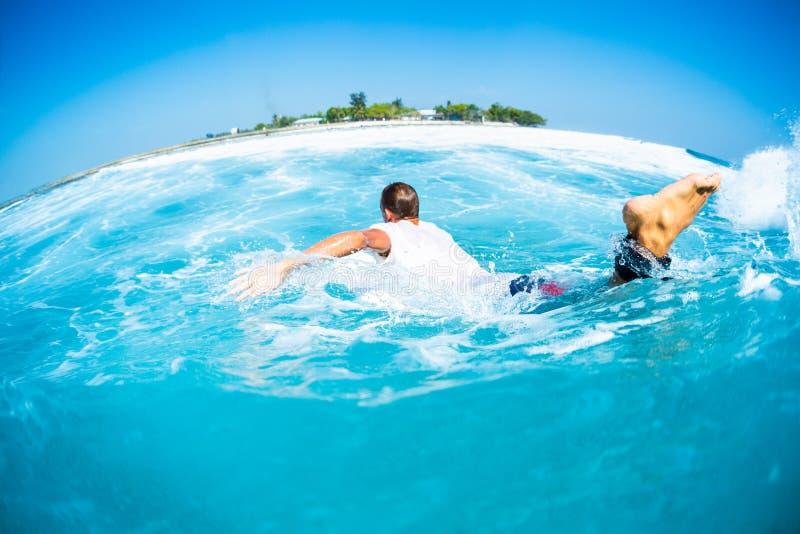 De surfer paddelt en stijgt de tropische oceaangolf op stock foto