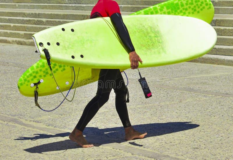 De surfer in wetsuit na opleiding en in handen houdt surfplanken stock afbeelding