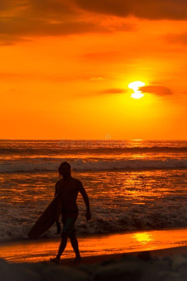 De surfermens van de strandzonsondergang het surfen levensstijl het ontspannen holdingssurfplank die oceaangolven voor branding b royalty-vrije stock foto