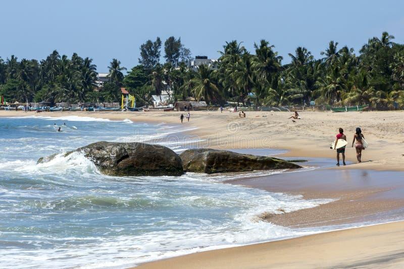 De surfers lopen voorbij Zeven Sterrots bij Arugam-Baai op de oostkust van Sri Lanka royalty-vrije stock foto