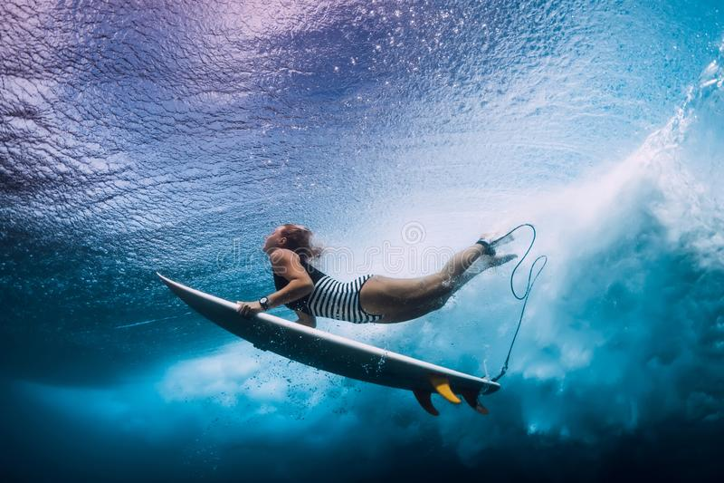 De surfervrouw duikt onderwater Surfgirl duikt onder golf stock afbeelding