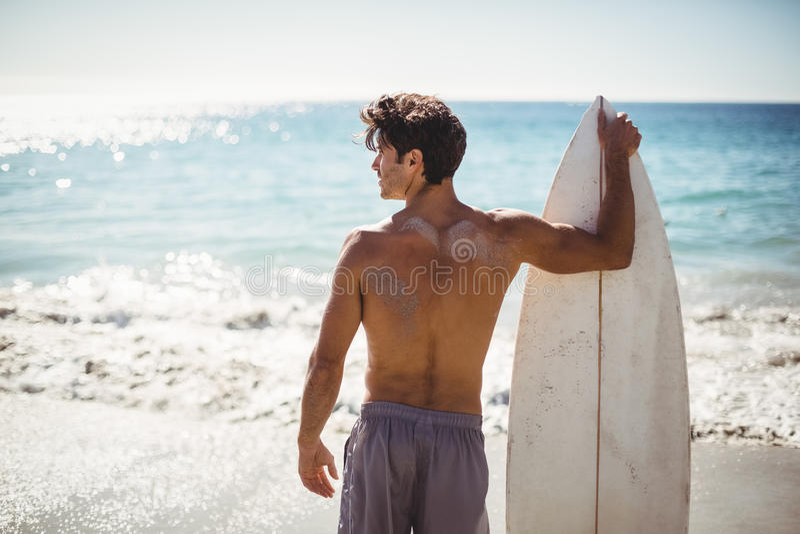 De surfplank van de mensenholding op strand royalty-vrije stock fotografie