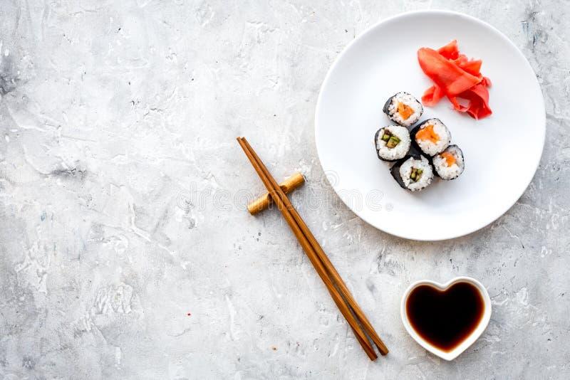 De sushi rollen met zalm en avocado op plaat met sojasaus, eetstokje, wasabi op grijze steen hoogste mening als achtergrond stock fotografie