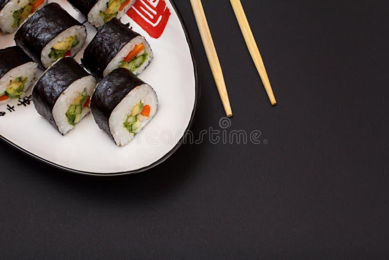 De sushi rolt in de bladen van het norizeewier op plaat met houten stokken op zwarte achtergrond royalty-vrije stock fotografie
