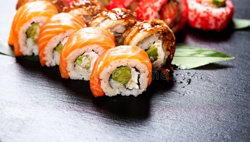 De sushi rolt close-up Japans voedsel in restaurant Broodje met zalm, paling, groenten en vliegende vissenkaviaar royalty-vrije stock afbeeldingen