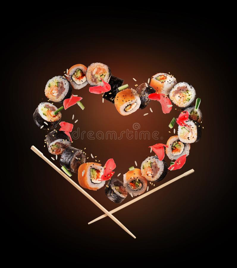 De sushi rolt met eetstokjes in de lucht in de vorm van het hart, op zwarte achtergrond worden bevroren die royalty-vrije stock foto's