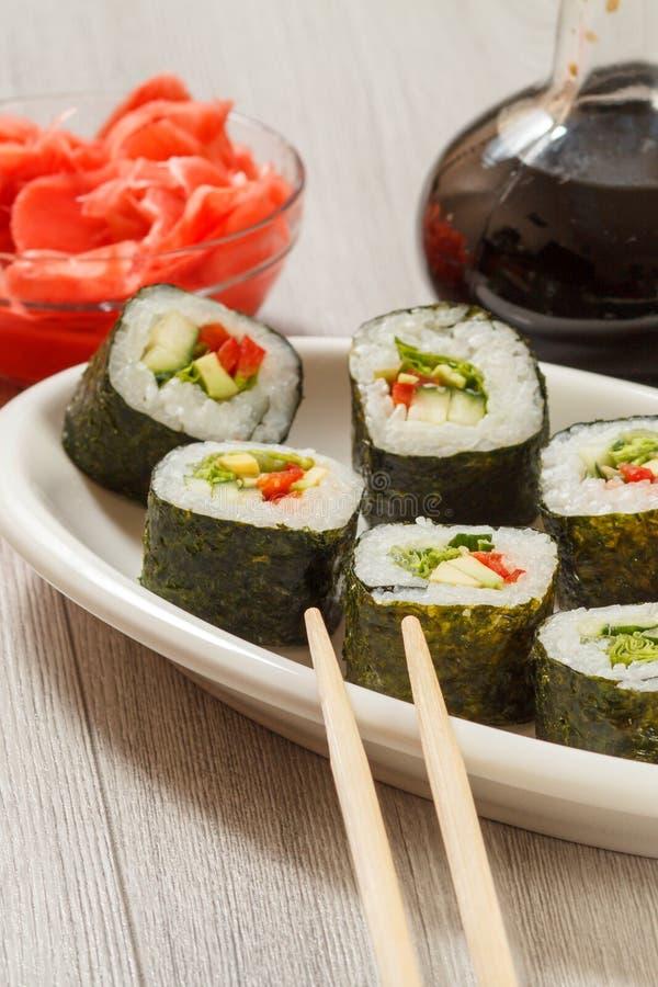 De sushi rolt met rijst op ceramische plaat, eetstokjes, glasfles met sojasaus en ingelegde gember in een kom royalty-vrije stock afbeeldingen