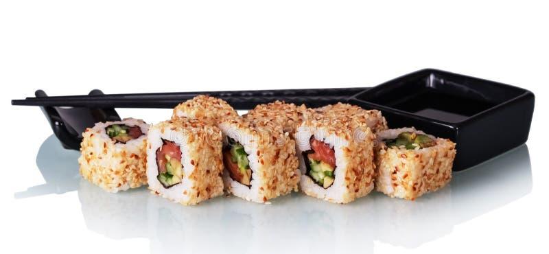 De sushi rolt met zalm en avocado in sesam, wasabikom en eetstokjes op wit wordt geïsoleerd dat royalty-vrije stock foto