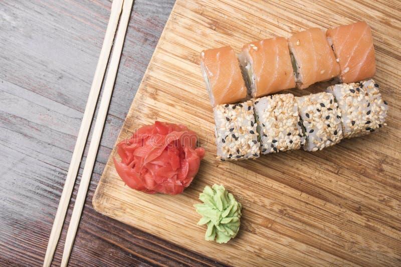 De sushi rolt met zalm en zwart-witte sesamzaden, gember, wasabi en sushistokken royalty-vrije stock afbeelding
