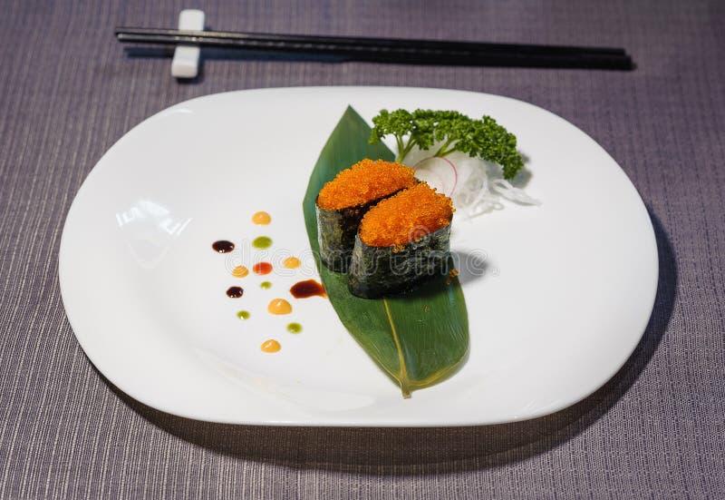 De sushi van de vissenkaviaar, schotel op bamboeblad wordt gediend, decoratieve sausen die stock afbeelding