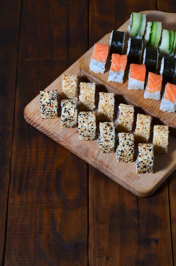 De sushireeks een aantal broodjes wordt gevestigd op een houten scherpe raad op een lijst in de keuken van een sushibar Een tradi stock foto