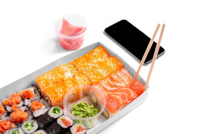 De sushireeks rolt op het witte van de de gembertelefoon van achtergrondeetstokjeswasabi concept van het de leveringsvoedsel stock foto's
