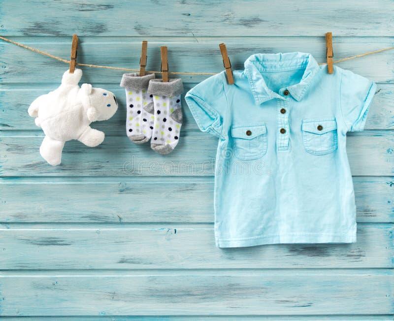 De t-shirt van de babyjongen, de sokken en het witte stuk speelgoed dragen op een drooglijn royalty-vrije stock fotografie