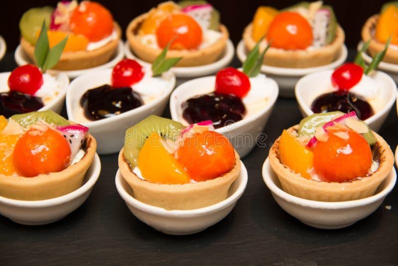 De taartjes van het fruitdessert met room, kiwi, en papaja stock foto's