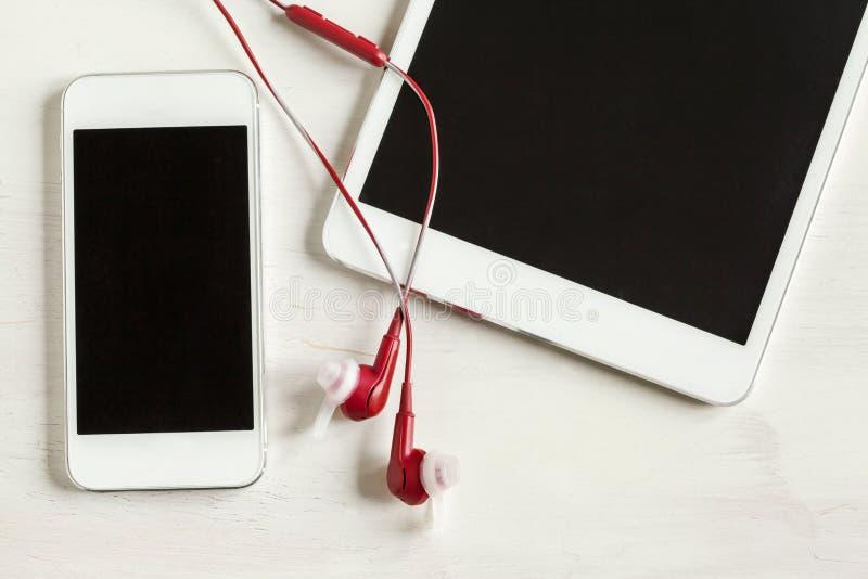 De tablet en de telefoon met hoofdtelefoons sluiten omhoog stock afbeeldingen