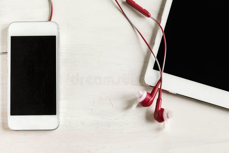 De tablet en de telefoon met hoofdtelefoons sluiten omhoog royalty-vrije stock fotografie
