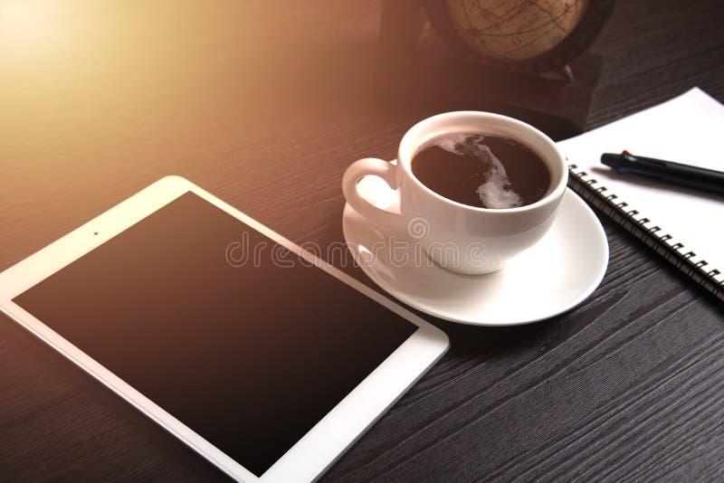De tablet en de zwarte koffie op houten lijst met Digitale Aardewereld brengen en oranje licht en lijnpunt, Notitieboekje en pen, stock afbeeldingen