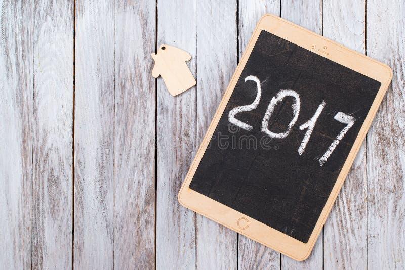 De tablet op houten achtergrond gelukkig nieuw het jaarconcept van 2017 Ruimte voor tekst stock fotografie