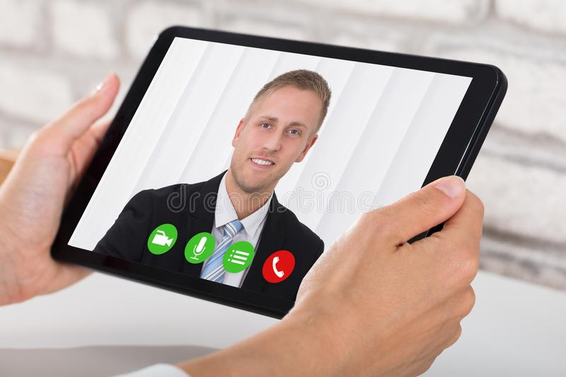 De Tablet van Businesspersonvideoconferencing on digital stock foto
