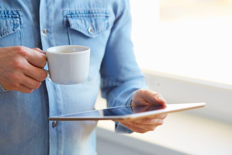 De tablet van de mensenholding en kop van koffie royalty-vrije stock foto