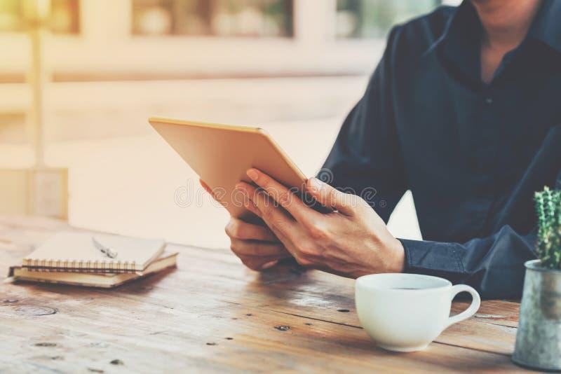 De tablet van de van bedrijfs Azië mensenholding op lijst in koffiewinkel met vi stock fotografie
