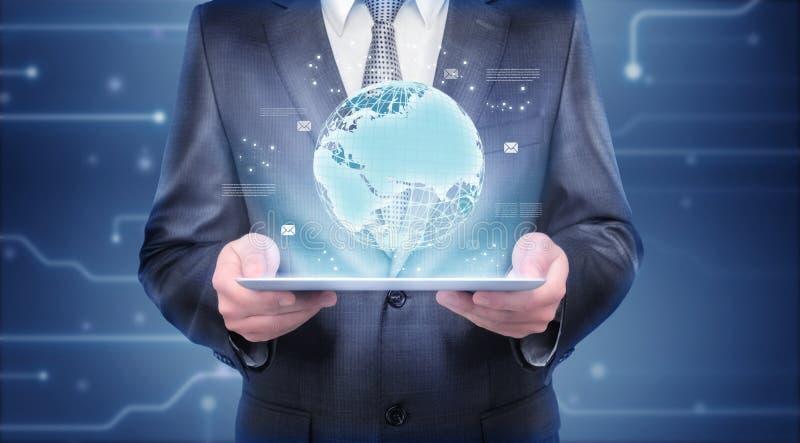 De tablet van de zakenmanholding die hologram van de Aarde toont royalty-vrije stock foto's
