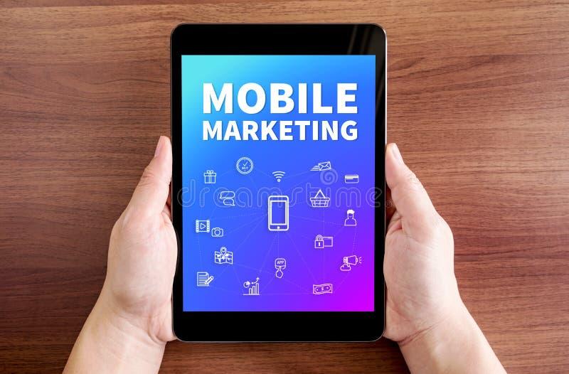De tablet van de twee handholding met Mobiele marketing en pictogram op het scherm stock fotografie