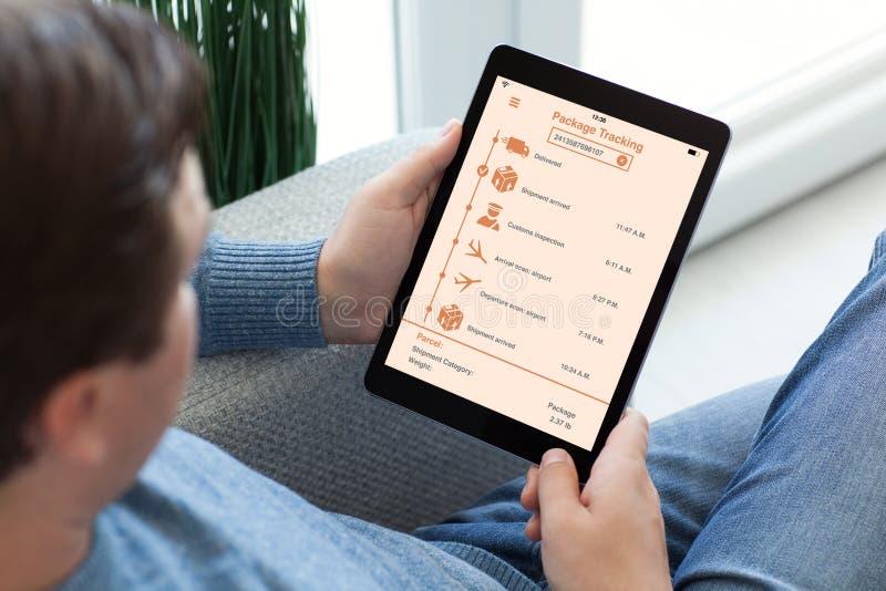 De tabletcomputer van de mensenholding met app volgend leveringspakket stock fotografie