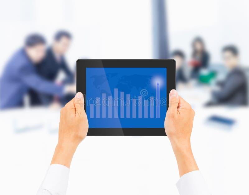 De tabletpc van de handholding met hogere financiële grafiek op zaken royalty-vrije stock foto's