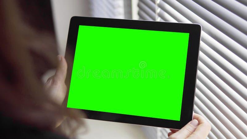 De Tabletpc van de meisjesholding dichtbij Jaloezie stock foto's