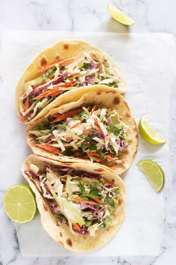 De taco's met guacamole en koolsla dienden met kalkplakken op een lichte achtergrond stock foto's
