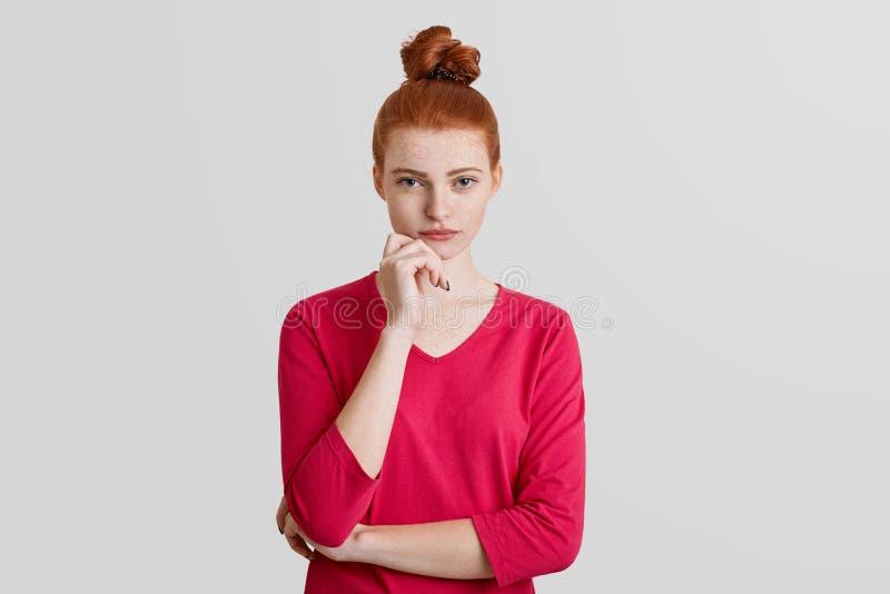De taille op portret van ernstig vrij vrouwelijk model met de knoop van het gemberhaar draagt rode sweater, houdt hand onder kin, stock afbeelding