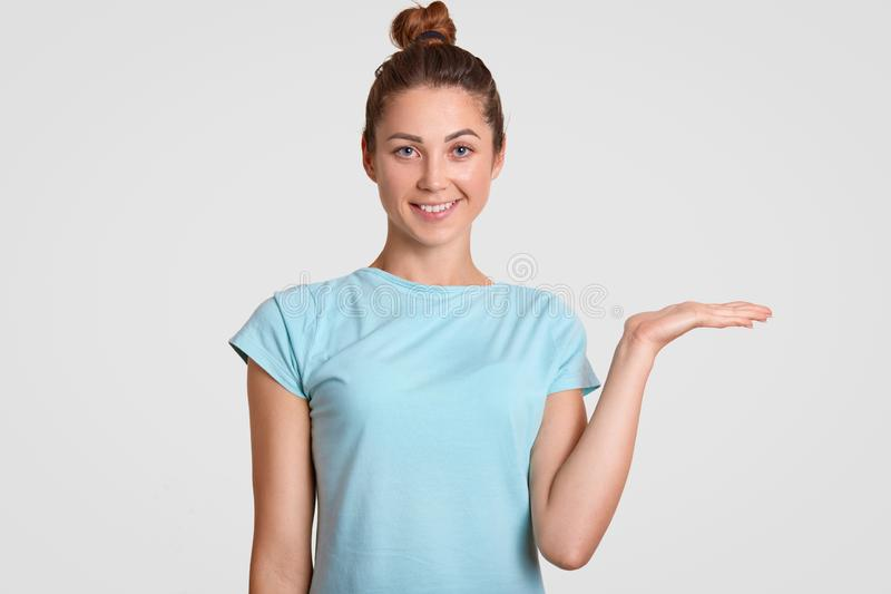 De taille op portret van knappe tiener houdt exemplaarruimte, houdt palm opgeheven, toont iets op vrije in casu geklede ruimte, stock foto's