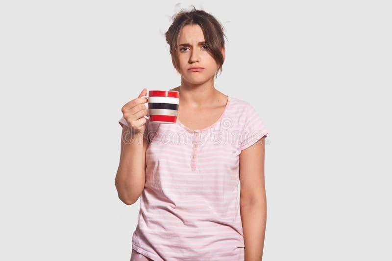 De taille op portret van ongelukkige vrouw heeft sombere slaperige uitdrukking, probeert te ontwaken, drinkt hete koffie, wil nie stock foto's