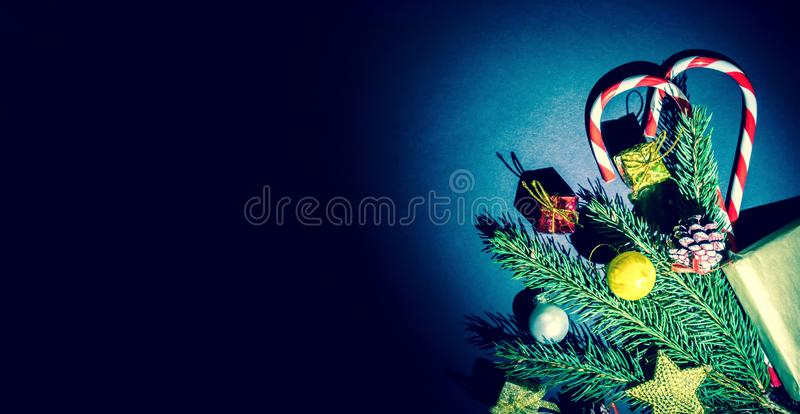 De tak van een Kerstboom met ballen, de sparappel, het traditionele suikergoed en de dozen met giften wodden achtergrond stock fotografie