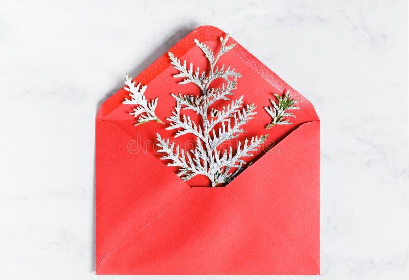 De takken van een thuja met rijp in een rode envelop wordt behandeld, minimale Nieuwjaars kaart die Vakantie, Gelukwens royalty-vrije stock foto