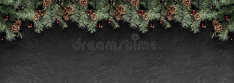 De takken van de Kerstmisspar met denneappels op donkere zwarte achtergrond Kerstmis en Gelukkige Nieuwjaarskaart, bokeh, het von stock afbeeldingen