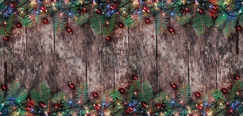 De takken van de Kerstmisspar met lichten en rode decoratie op houten achtergrond Kerstmis en Gelukkige Nieuwjaarsamenstelling royalty-vrije stock fotografie