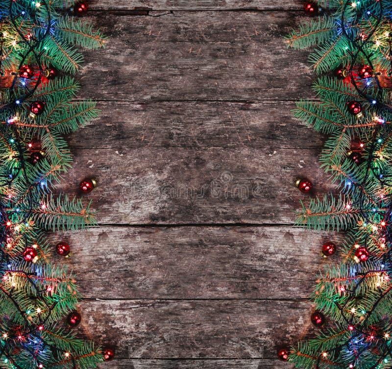 De takken van de Kerstmisspar met lichten en rode decoratie op houten achtergrond Kerstmis en Gelukkige Nieuwjaarsamenstelling stock fotografie