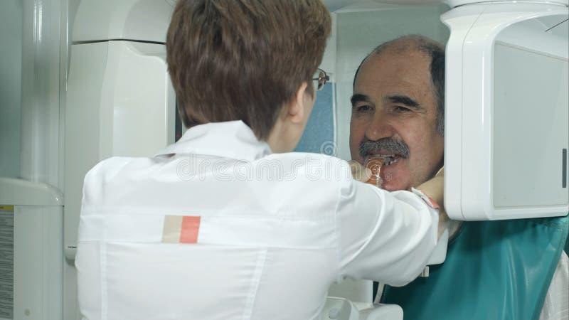 De tand hogere patiënt ondergaat panoramisch schedelaftasten van tanden royalty-vrije stock foto's