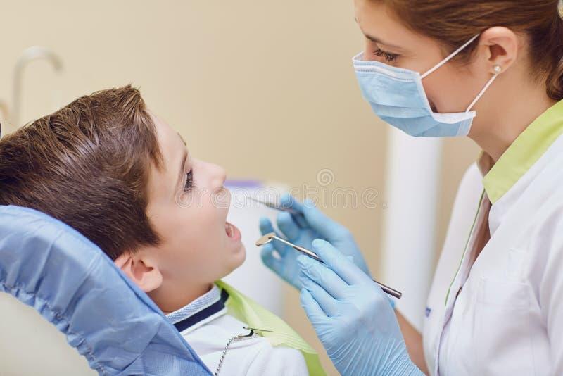 De tandarts behandelt de tanden van een kind aan een jongen in een tandbureau royalty-vrije stock afbeelding