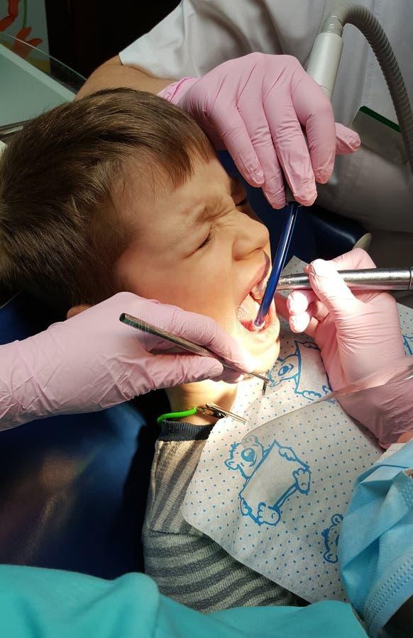 De tandarts behandelt tanden van weinig jongen in kliniek stock foto's