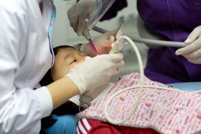 De tandarts doet tandenreparatie voor Aziatisch jong geitje royalty-vrije stock foto