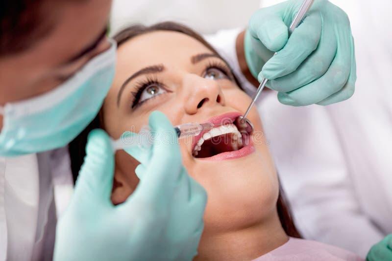 De tandarts geeft spuit verdooft aan zijn patiënt stock afbeelding
