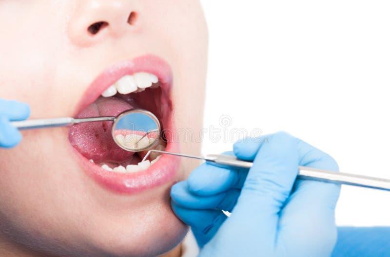 De tandarts onderzoekt de mond van een wijfje met tandspiegel stock afbeeldingen