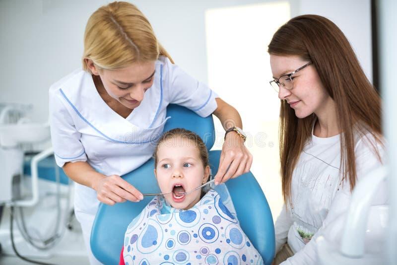 De tandarts onderzoekt tanden van een klein meisje royalty-vrije stock fotografie