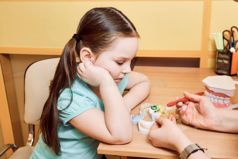 De tandarts toont een klein meisje hoe te om het gebit schoon te maken stock foto